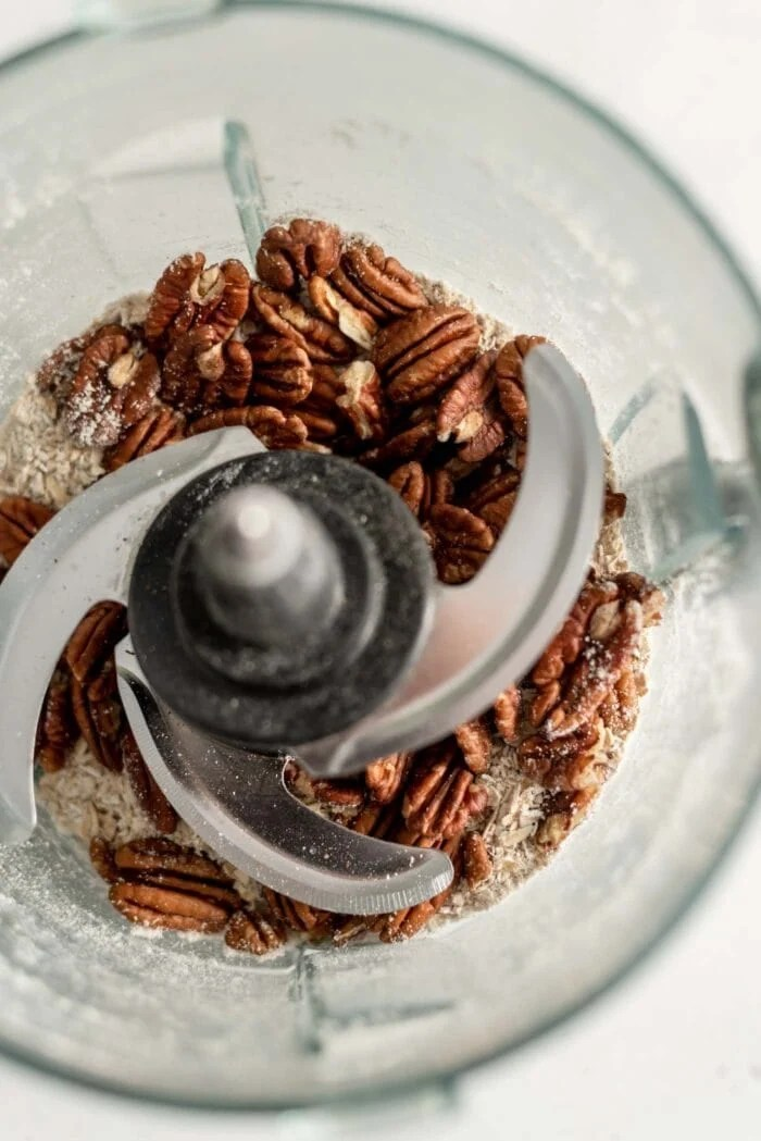 Oat flour and pecans in a food processor.