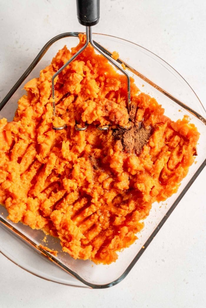 Mashed sweet potato with maple syrup in a baking dish.