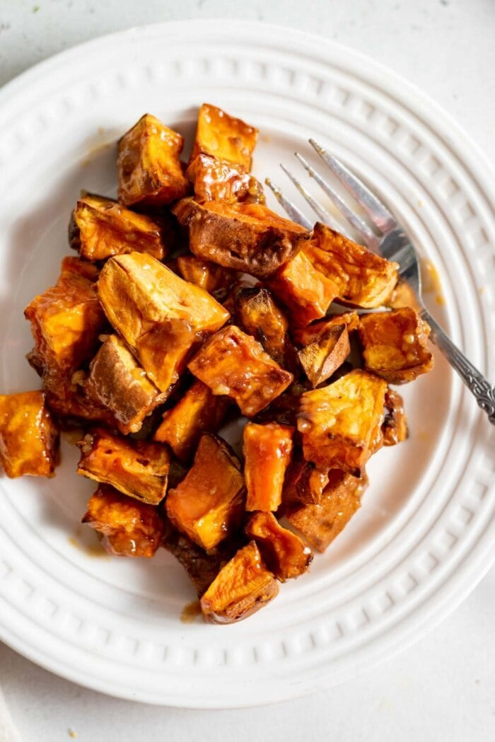 Miso glazed sweet potato on a small white plate.