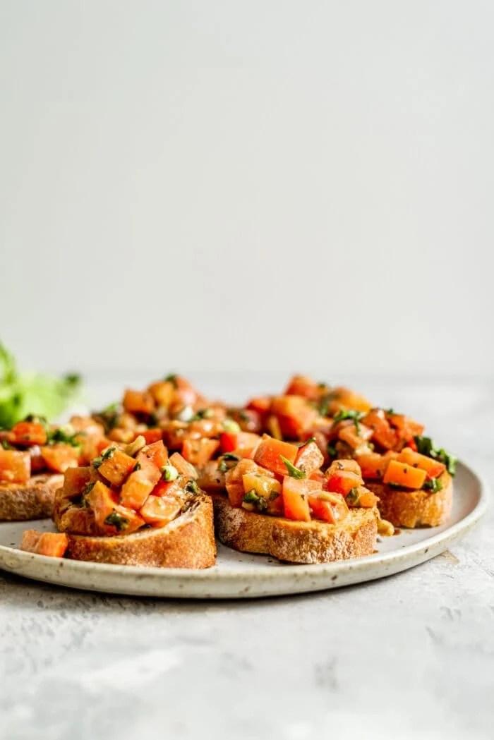 Pieces of vegan bruschetta on a plate.
