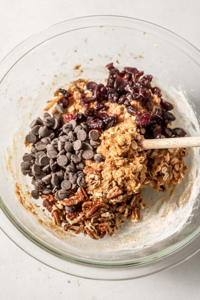 Raw cookie batter with cranberries, chocolate chips and pecans being mixed in.