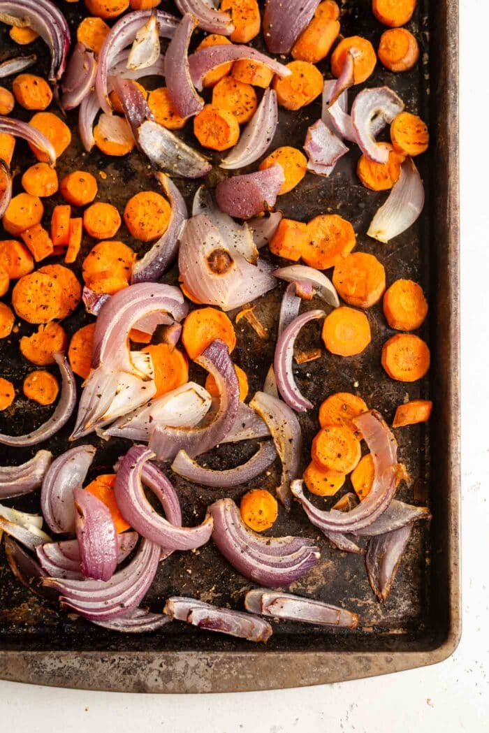 Roasted carrots and onions on a baking tray.