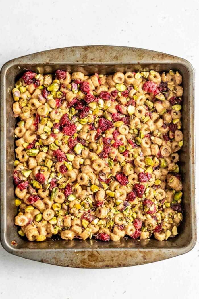 Cereal bars topped with cranberries and pistachios pressed into a small tin baking dish.