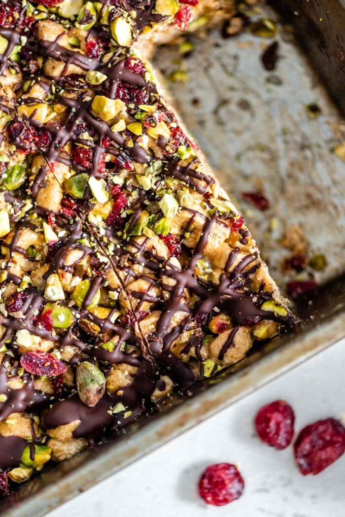 A close up of vegan cereal bars in a baking tray with cranberries, pistachios and chocolate on top.