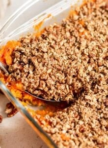 Scooping out a serving of sweet potato casserole out of a baking dish.