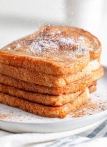 A big stack of french toast sprinkled with powdered sugar.