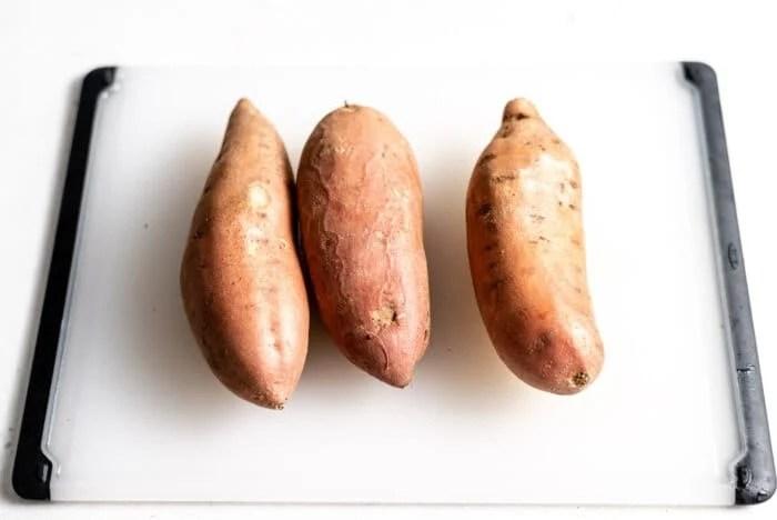 3 whole sweet potatoes on a cutting board.