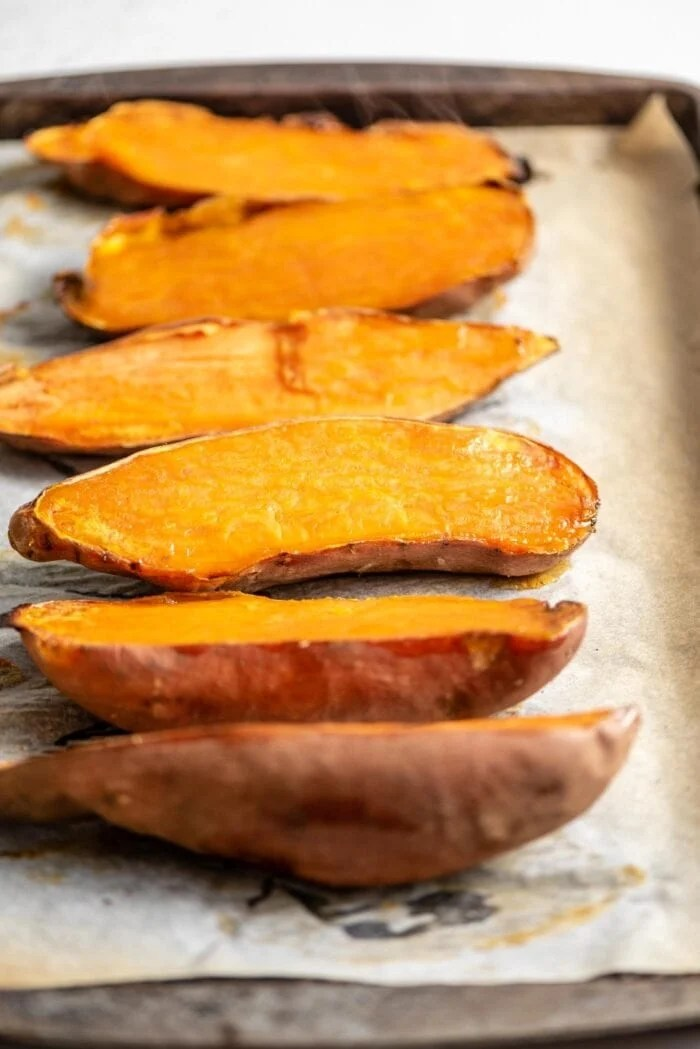 6 baked sweet potato halves on a baking tray lined with parchment paper.
