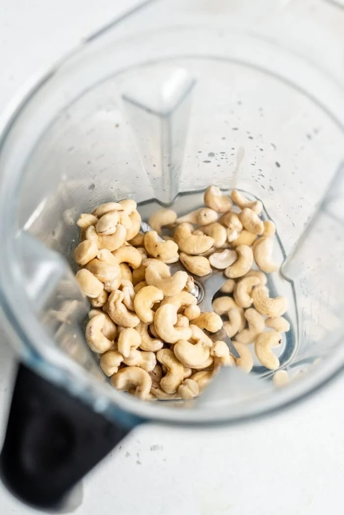 Raw cashews in a blender with water.