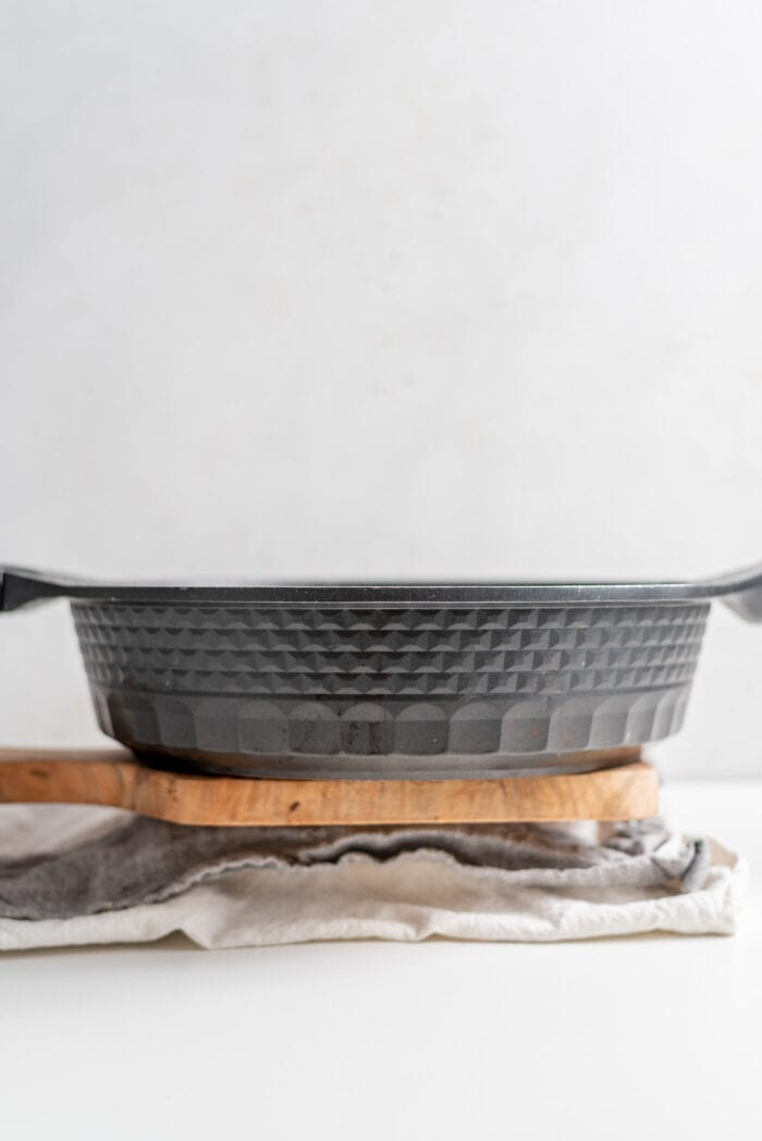 A black frying pan sitting on a block of tofu wrapped in a dish cloth.