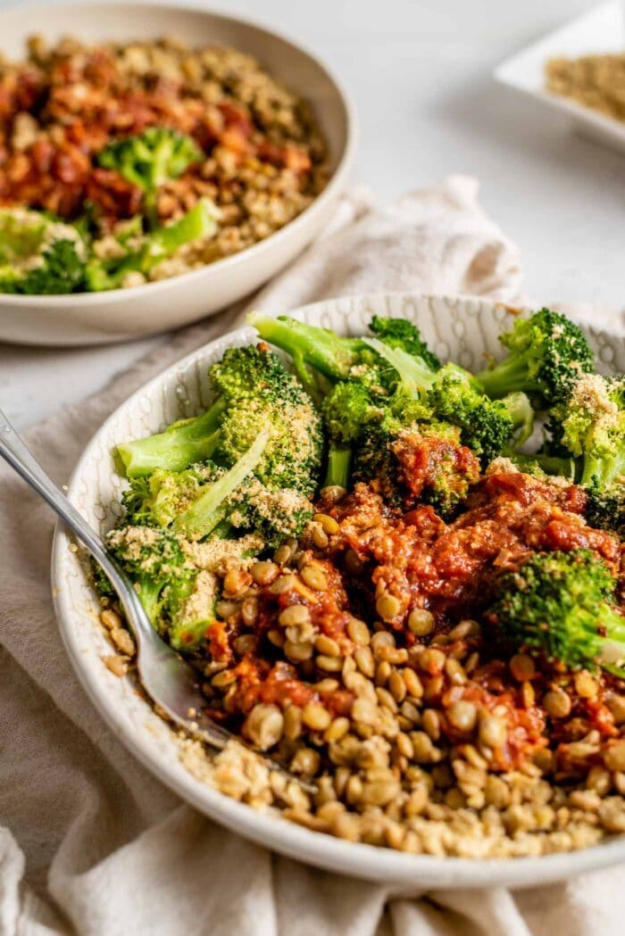 A bowl with steamed broccoli, vegan parmesan, lentils and marinara sauce.