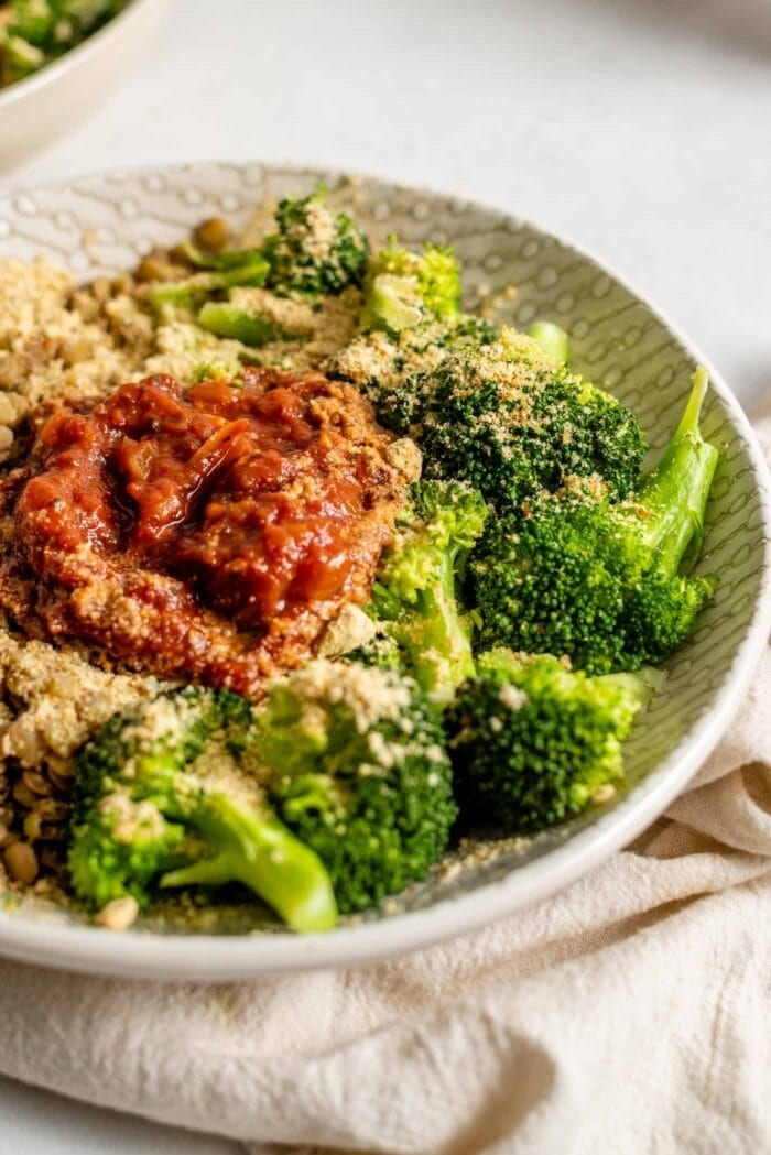 Steamed broccoli in a bowl with lentils and marinara sauce.