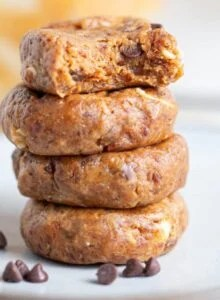 A stack of 4 raw peanut butter cookie with a few chocolate chips sprinkled around them.