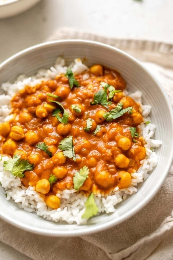A bowl of chickpea tikka masala over rice topped with cilantro.