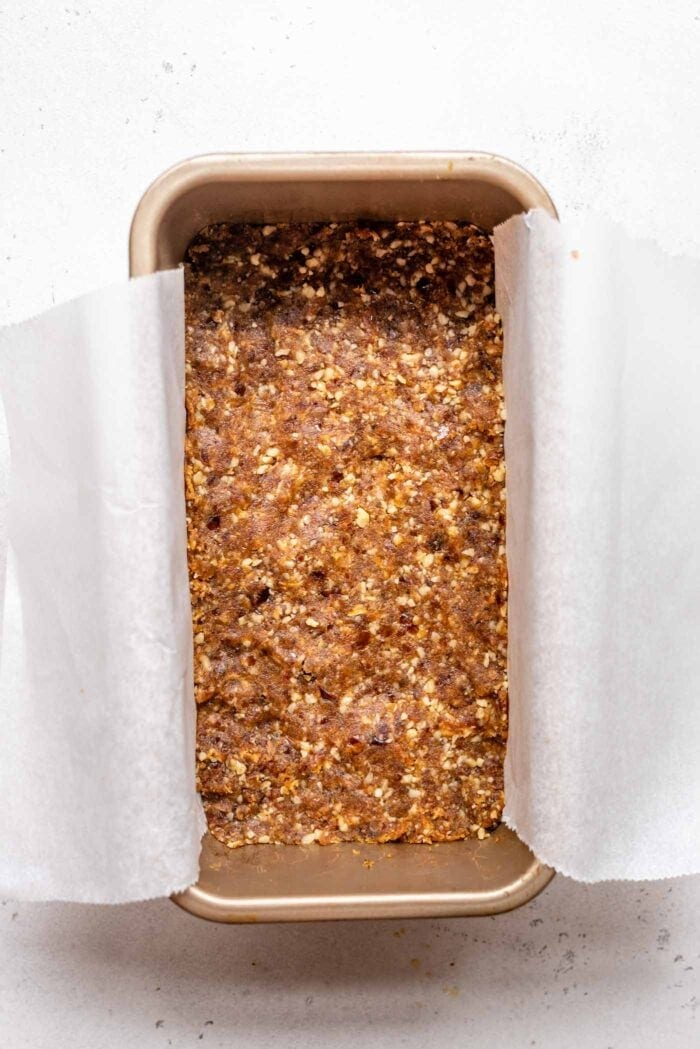 A raw walnut date crust pressed into a loaf pan lined with parchment paper.