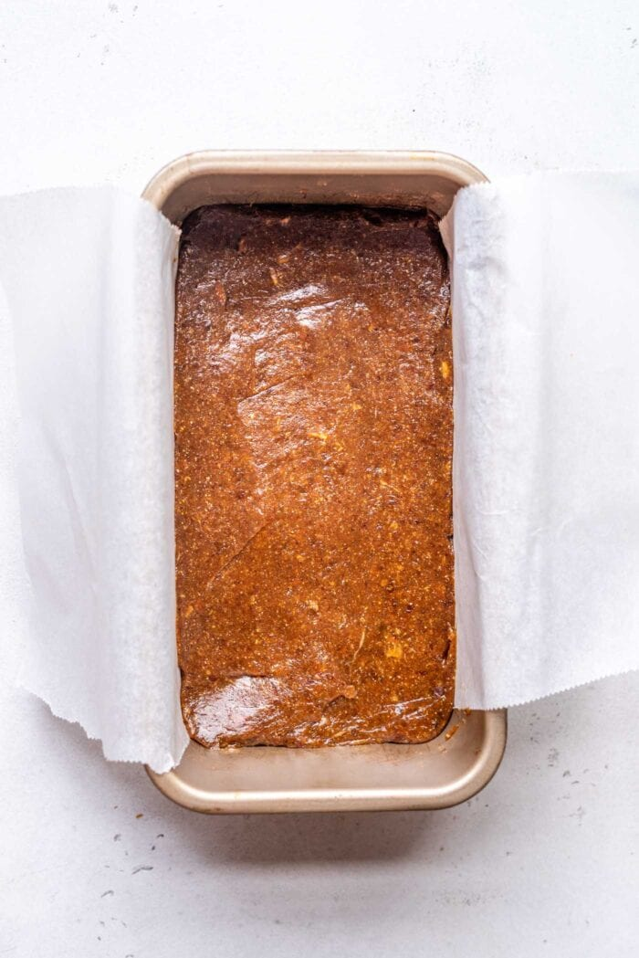 Date caramel spread in a loaf pan lined with parchment paper.
