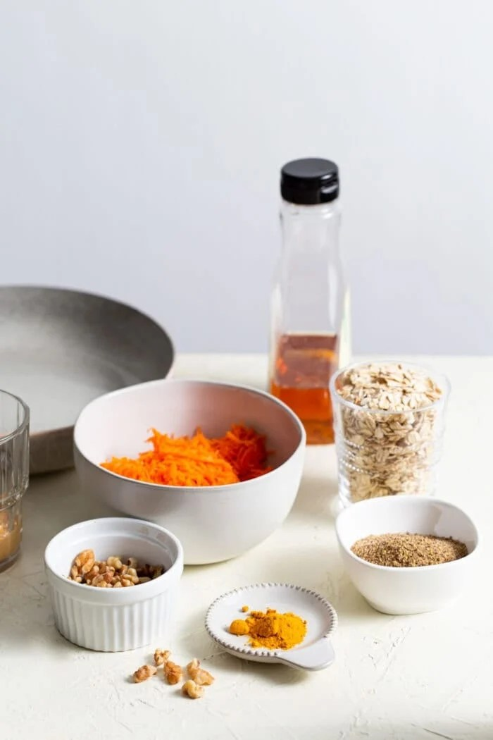 Carrots, walnuts, oats, maple syrup and turmeric in small dishes on a counter top.