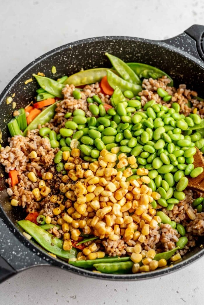 Corn, farro, edamame, carrots and snow peas in a skillet.