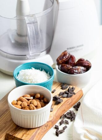 Almonds, coconut, dates and chocolate chips in containers on a countertop.