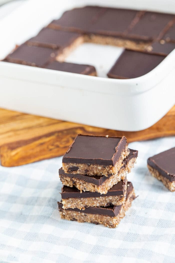 A stack of 4 almond coconut bars topped with chocolate.