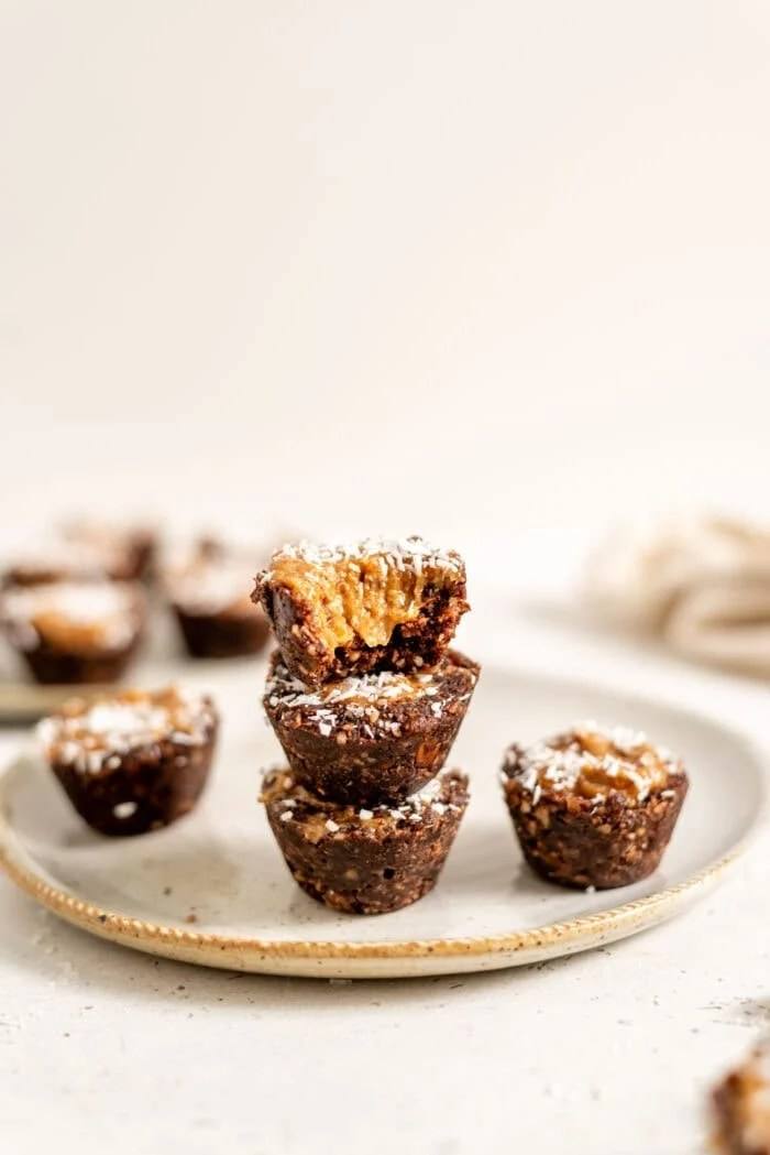 A stack of 3 chocolate caramel tarts on a small plate.