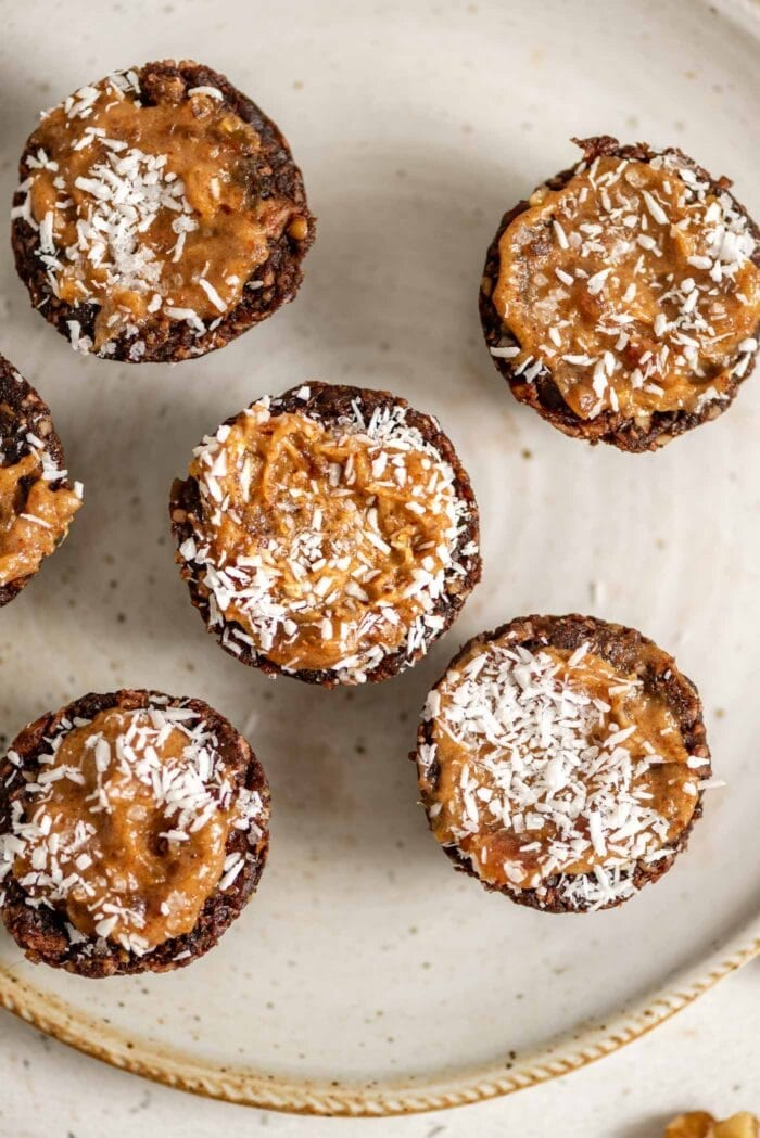 Chocolate tarts with a caramel filling topped with coconut on a small plate.