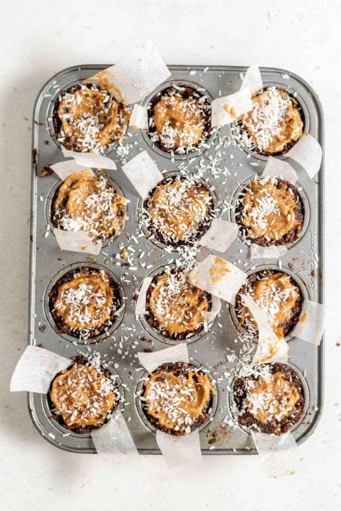 Caramel tarts topped with coconut in a muffin tin.