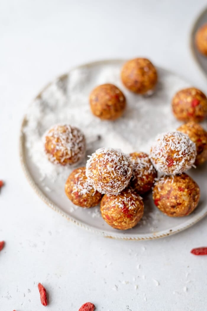 Orange energy balls rolled in coconut on a small plate with some goji berries in the foreground.