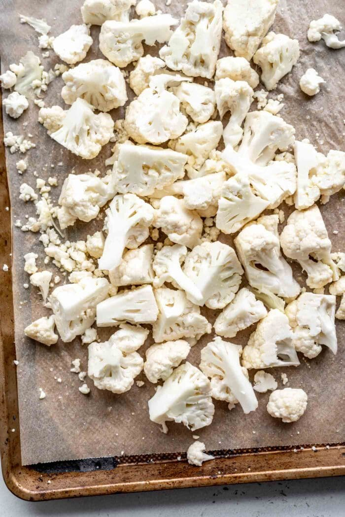 Chopped cauliflower on a lined baking tray.