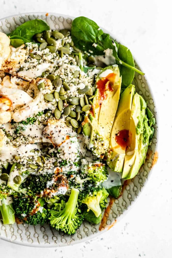 Avocado, roasted cauliflower, broccoli, spinach and seeds topped with tahini dressing in a bowl.