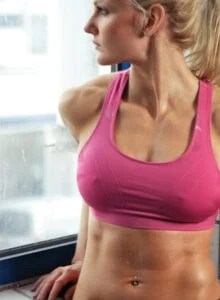 Fit woman in a sports bra looking out a window.