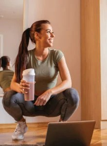 Fit woman with a shaker cup crouched over a laptop.