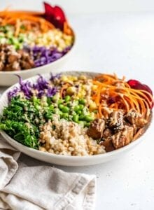Brown rice, edamame, tempeh, carrot, corn, kale and red cabbage in a bowl topped with sauce and sesame seeds.