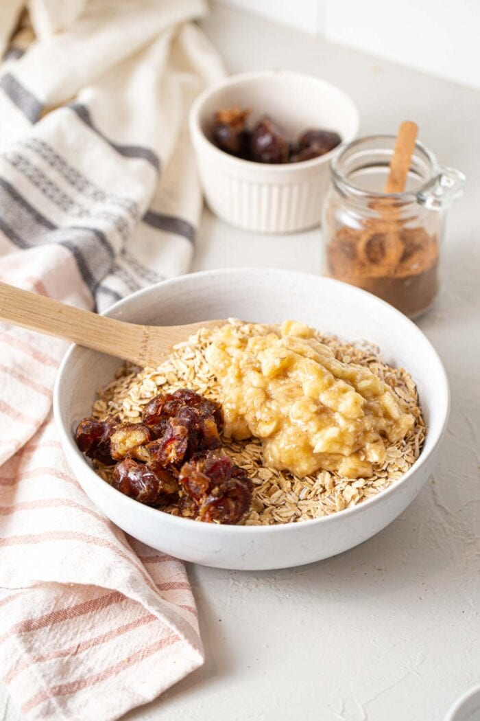 A bowl of oats topped with mashed banana and chopped dates.