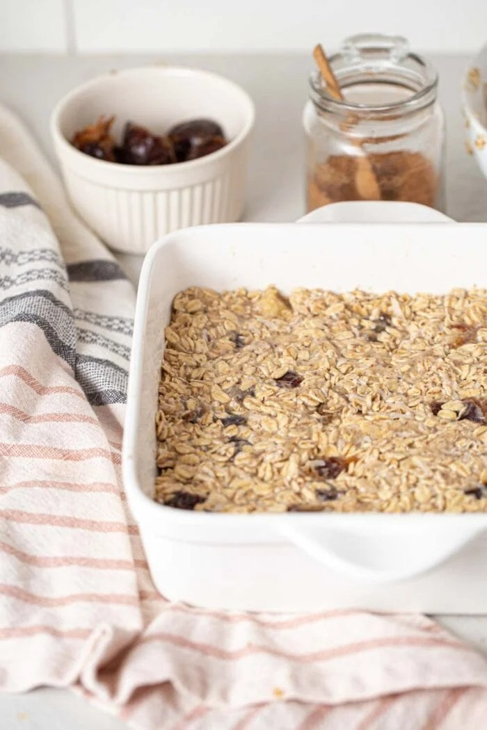 Raw oatmeal dough with banana and dates in a baking pan.