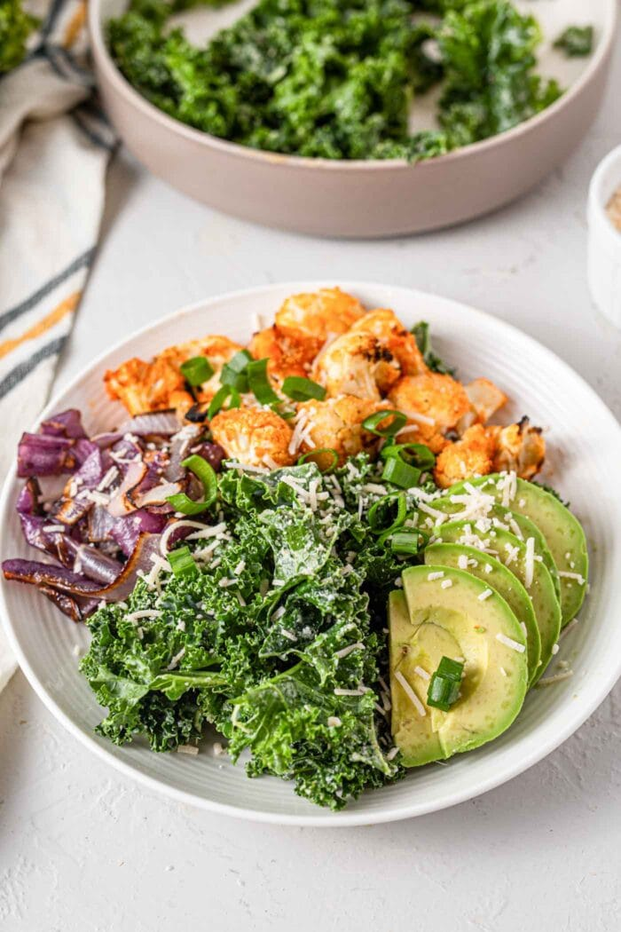 A bowl of kale, avocado, buffalo cauliflower, roasted onions and parmesan.
