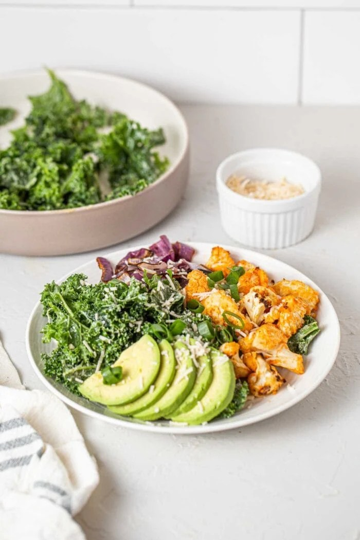 Avocado, buffalo cauliflower, roasted red onion and kale in a bowl.