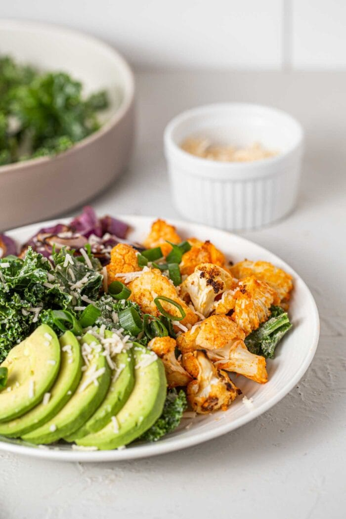 A kale salad topped with buffalo cauliflower and avocado.