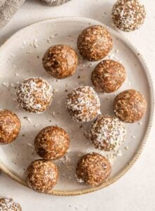 A plate of energy balls rolled in shredded coconut.