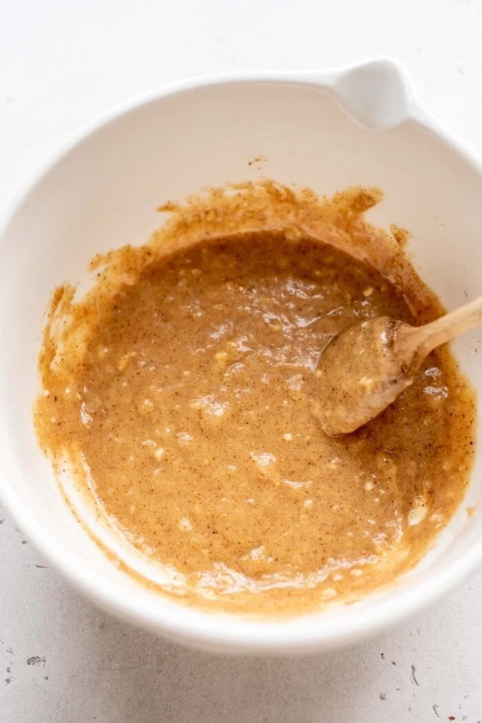 Mashed banana mixed with almond butter in a mixing bowl with a spoon.