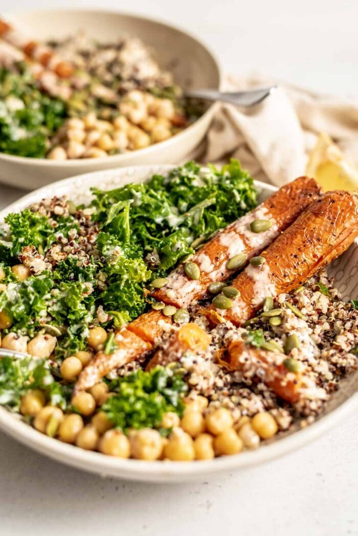 A bowl of carrots, quinoa, pumpkin seeds, kale and chickpeas.