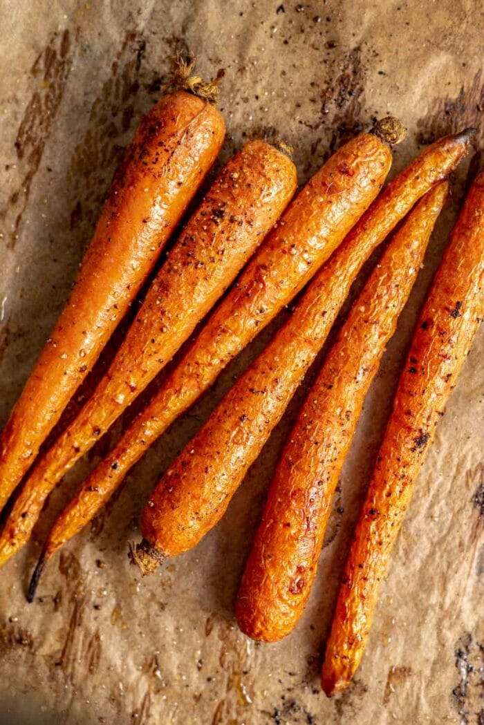 6 roasted carrots on a baking tray.