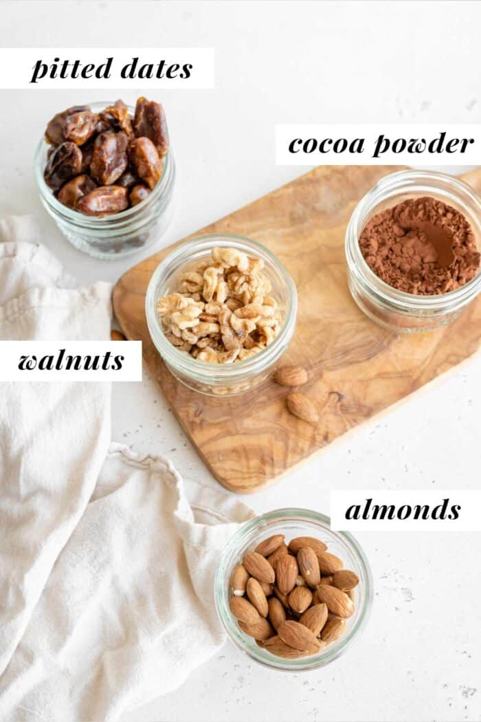 Dates, walnuts, almonds and cocoa powder in jars.