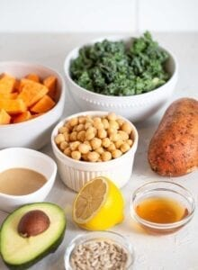 Kale, chickpeas, sweet potato, lemon and avocado on a counter.