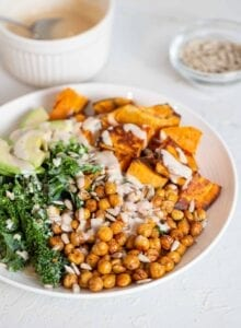 A kale, roasted chickpea, sweet potato and avocado salad in a bowl.