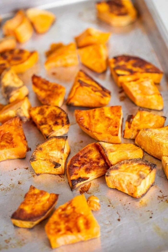 Roasted sweet potatoes on a baking tray.