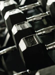 Multiple black rubber dumbbells on a rack.