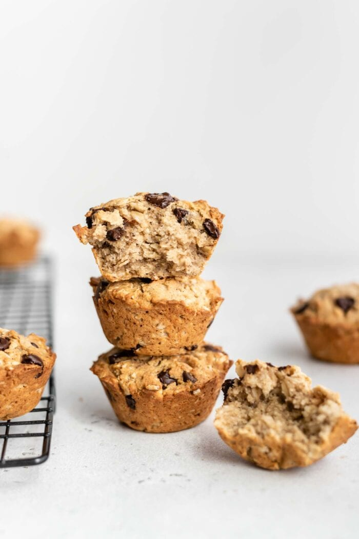 A stack of 3 chocolate chip muffins with a bite taken out of the one on top.