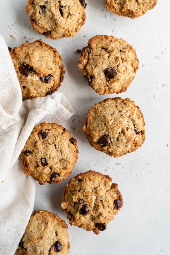 An overhead image of 8 chocolate chip muffins on a counter with a dishcloth beside them.