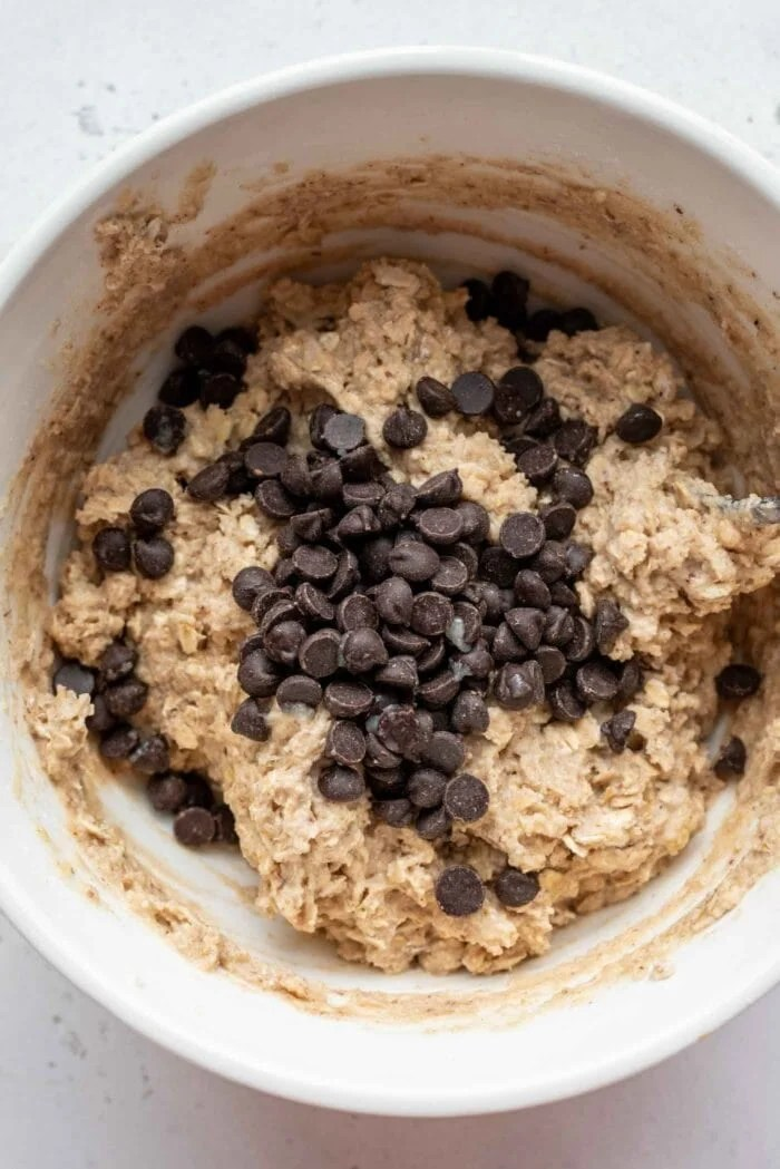 Chocolate chips being added to a mixing bowl of muffin batter.